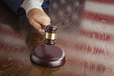 Judge Slams His Gavel and American Flag Table Reflection.