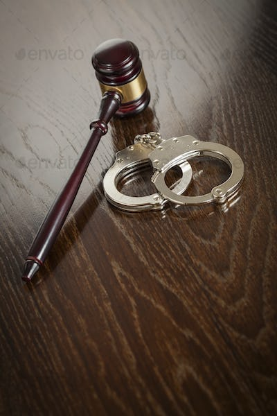 Gavel and Pair of Handcuffs on Wooden Table.
