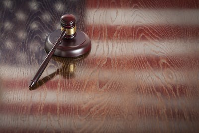 Wooden Gavel Resting on American Flag Reflecting Table.