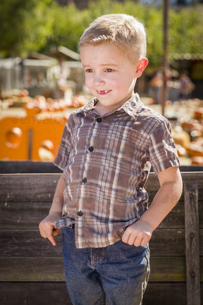 Little Boy at Pumpkin Patch With Hands in His Pockets Leaning on Antique Wood Wagon
