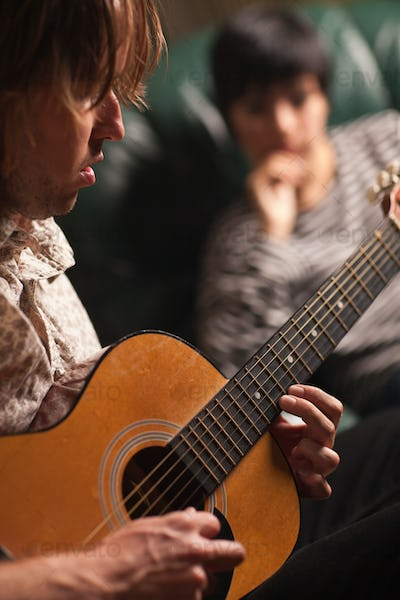 Young Musician Plays His Acoustic Guitar as Friend in the Background Listens.