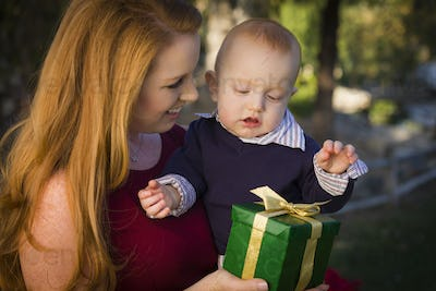 Beautiful Young Mother and Smiling Baby with Wrapped Christmas Gift.