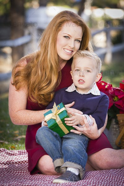 Handsome Young Boy Holding Christmas Gift with His Mom in the Park.