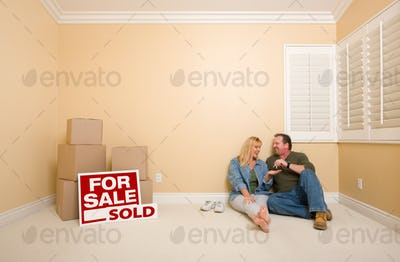 Excited Couple With New Keys Relaxing on Floor Near Boxes and Sold Real Estate Signs in Empty Room.