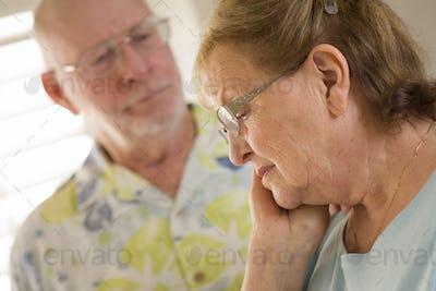 Senior Adult Man Consoles Sad Senior Adult Female.