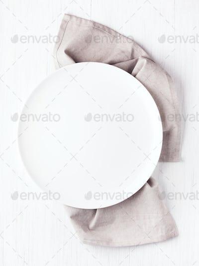 Empty Plate on Linen Napkin on White Table.