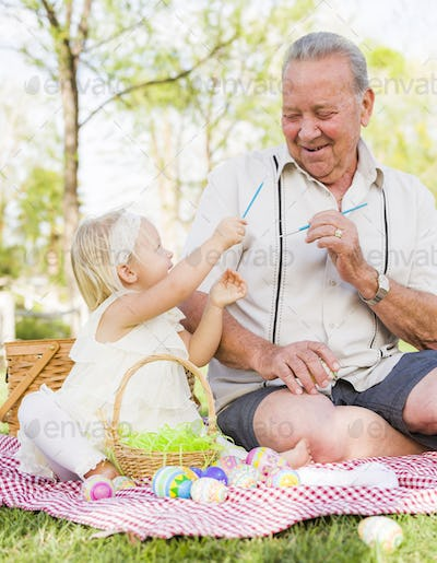 Loving Grandfather and Granddaughter Coloring Easter Eggs Together on Picnic Blanket At The Park.