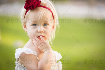 Beautiful Adorable Little Girl With Her Hand On Her Face Wearing White Dress In A Grass Field.