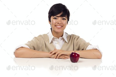 Smiling Mixed Race Young Adult Female Sitting at White Table with Apple Isolated