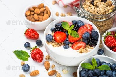 Greek yogurt granola with fresh berries on white table