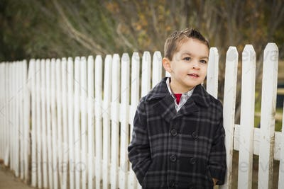 Young Mixed Race Boy Waiting For School Bus Along Fence Outside.