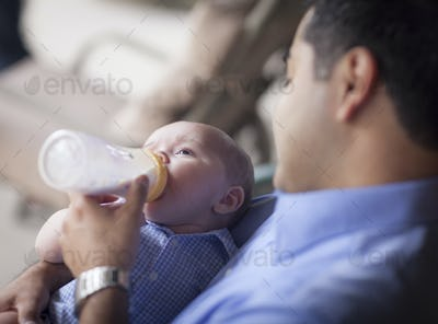 Happy Hispanic Father Bottle Feeding His Very Content Mixed Race Son.