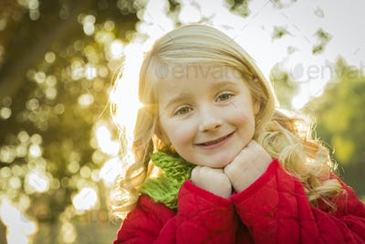 Sweet Little Girl Wearing Winter Coat and Scarf Outdoors at the Park.