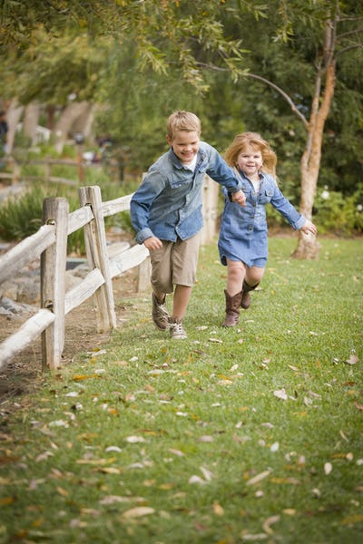 Happy Young Brother and Sister Running Together Outside.