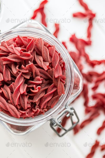 Uncooked colorful pasta with beetroot flavor