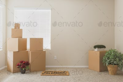 Variety of Packed Moving Boxes and Potted Plants and Welcome Mat In Empty Room with Room For Text.