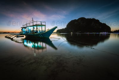Tropical harbor sea bay with banca boat in evening. Blue hour in lagoon in Philippines, Palawan, El