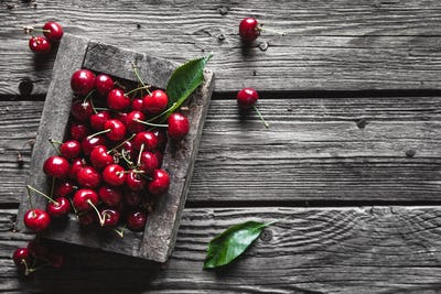 Cherries in a wood crate over a wood background in an old wooden box, healthy food, fruit