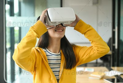 Asian girl wearing a yellow shirt is using the VR headset. She is smiling.