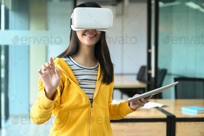 Asian girl is wearing yellow shirt, using VR headset. She hold laptop and point hand at the front.