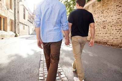 Rear View Of Male Gay Couple On Vacation Holding Hands Walking Along City Street