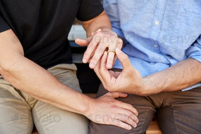 Close Up Of Man Proposing To Male Partner With Ring