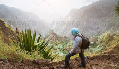 Traveler with backpack looking over the rural landscape with mountain peaks and ravine in dust air