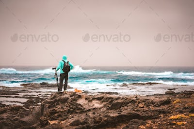 Photograph with a dog looking for motive. Waves hitting volcanic rocky coastline. Sahara dust in the