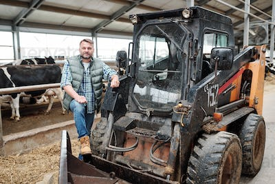 Worker of farmhouse standing by tractor while cleaning aisle of animal farm