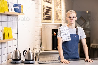 Young male barista in uniform standing by table with working equipment