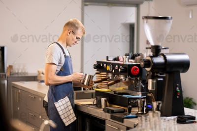 Young barista standing by coffee machine while preparing drinks for clients