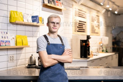 Young cross-armed barista or owner of cafeteria standing by table