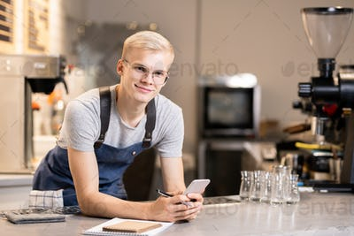 Happy waiter with pen and smartphone standing by workplace in front of camera