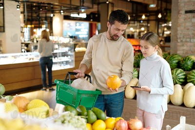 Young father with basket consulting with daughter while both choosing ripe melon
