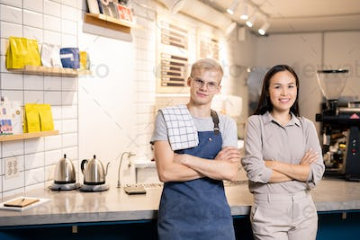 Young successful waiters in uniform looking at you while standing by workplace