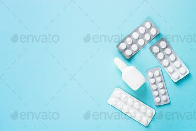 Pills on blue background top view