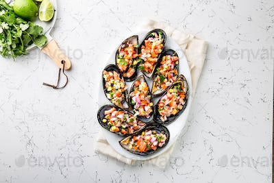 Choros a la chalaca. Big mussels seasoned with purple onion, tomatoes, corn and lemon