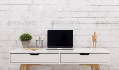 Modern laptop with black blank screen on white office table