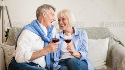 Loving senior couple drinking wine at home