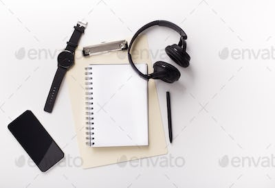 Cellphone, notebook and headphones on white background
