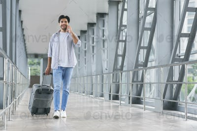 Young tourist talking on phone, walking in luggage in airport