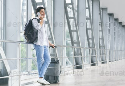 Millennial guy talking on phone, waiting for flight with luggage at airport