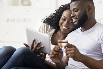 African American Couple Shopping Online Using Digital Tablet At Home
