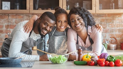 Cheerful african family having good time while cooking