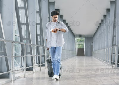 Worried tourist checking time on watch, going in airport walkway