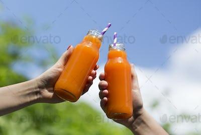 Orange fresh detox drink in girls hands over blue sky