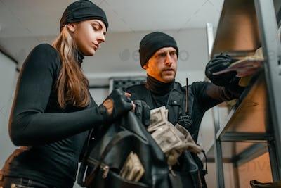 Robbers in black uniform steals money from vault