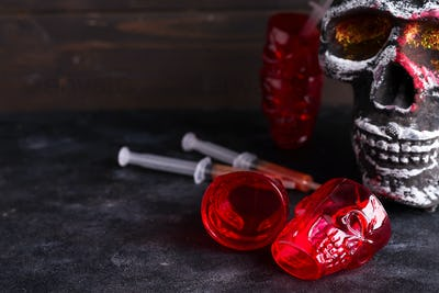 Medical syringes with tomato juice and a human skeleton face as cup on black background