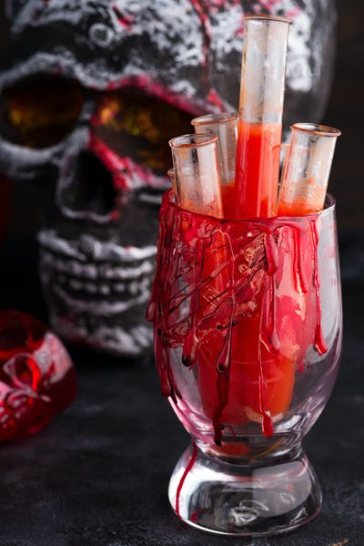 Halloween bloody glass with tomato juice and a human skeleton face as cup on black background