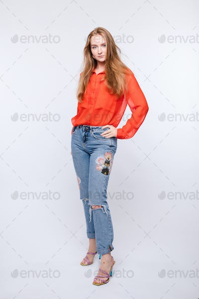 Girl in red blouse and jeans posing on isolated background
